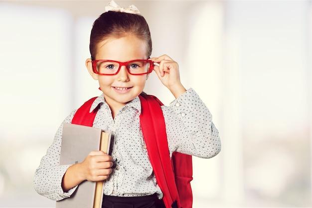 Piccola studentessa carina con gli occhiali con il libro sullo sfondo
