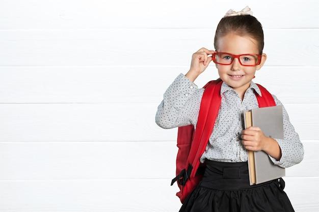 Piccola studentessa carina con gli occhiali con il libro