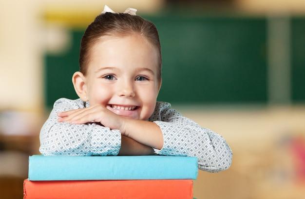 Piccola studentessa carina con libri sullo sfondo della lavagna