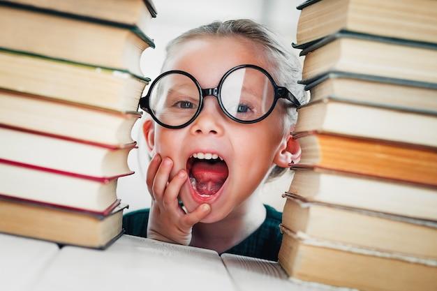 La scolaretta carina con i libri si prepara per le lezioni ispirando l'istruzione privata o domestica