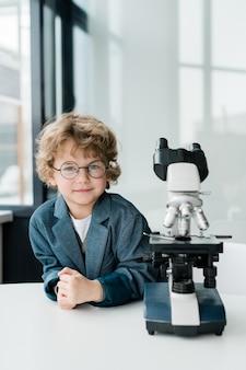 Piccolo scienziato sveglio in occhiali da vista e abbigliamento formale che ti guarda mentre è in piedi dal microscopio sul posto di lavoro