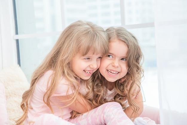 Fratelli germani piccoli svegli che si siedono sul davanzale della finestra a casa che abbraccia, ritratto di bambine graziose sul davanzale della camera in inverno. adorabile bambino pensieroso in rosa.