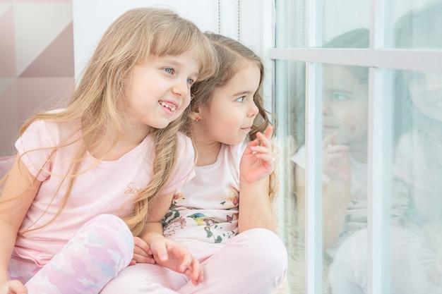 Fratelli piccoli svegli che si siedono sul davanzale della finestra a casa guarda fuori dalla finestra alla neve, ritratto di bambine graziose sul davanzale della camera in inverno. adorabile bambino pensieroso in rosa, bambino carino durante la contemplazione.