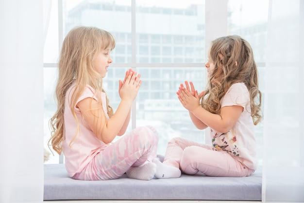 Sorelline sveglie che si siedono sul davanzale della finestra a casa che giocano tra loro, ritratto di bambine graziose vestite di abbigliamento casual da casa bianco e rosa sul davanzale della stanza in inverno.