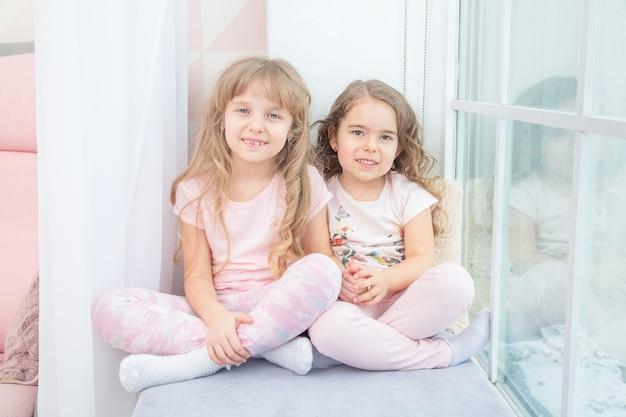 Sorelline sveglie che si siedono sul davanzale della finestra a casa, ritratto di bambine graziose sul davanzale della stanza in inverno.