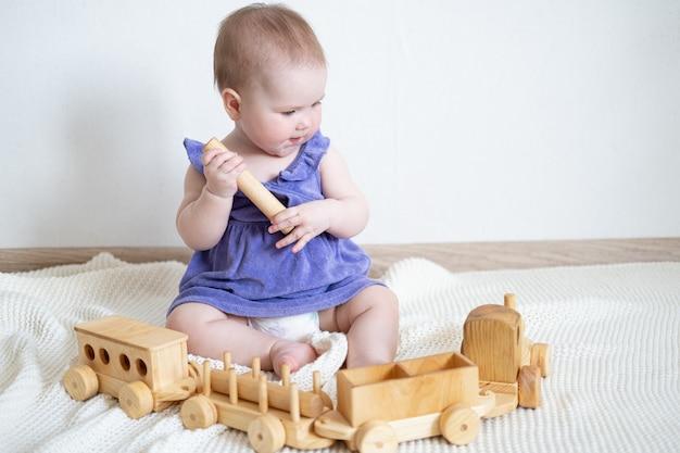 Piccola neonata caucasica sorridente sveglia che gioca con il treno di legno. giocattoli per bambini piccoli. sviluppo iniziale