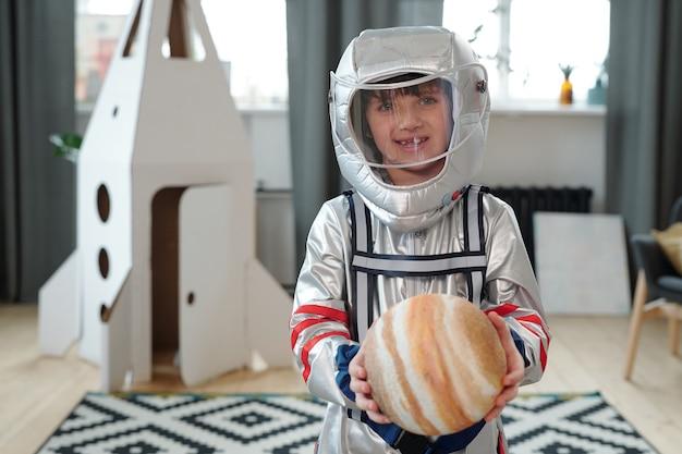Simpatico astronauta che tiene uno dei pianeti durante il gioco