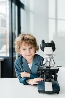 Carino piccolo scienziato di successo che ti guarda stando in piedi dal microscopio in classe o in laboratorio