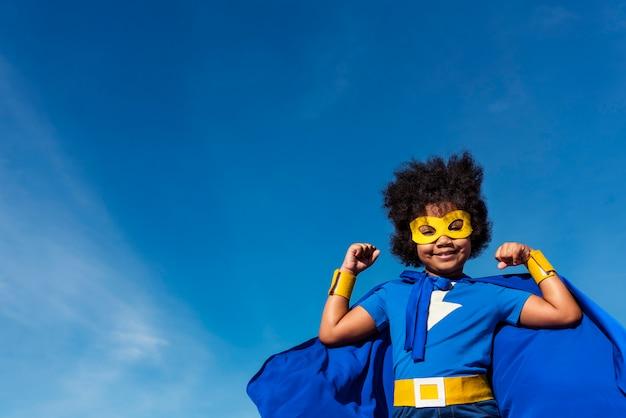 Ragazza carina piccolo supereroe con afro