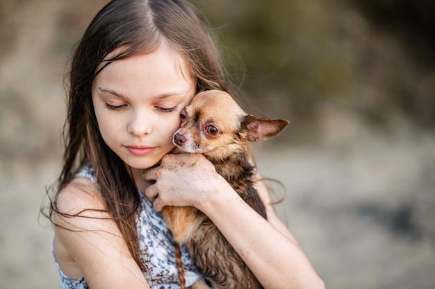 La piccola ragazza teenager sveglia abbraccia il suo cane. ritratto di un bambino con un chihuahua. una ragazza con i capelli lunghi mostra amore e sentimenti teneri per un animale domestico. un cane di razza nelle mani del suo proprietario.