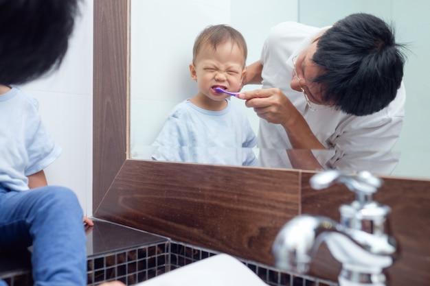 Denti di spazzolatura del piccolo bambino sveglio del ragazzo del bambino con il papà in bagno