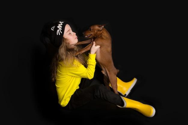 Una graziosa bambina abbraccia il suo cane, il miniature pinscher. riprese in studio su sfondo nero. il concetto di amore per la natura, protezione degli animali, innocenza, divertimento. foto di alta qualità