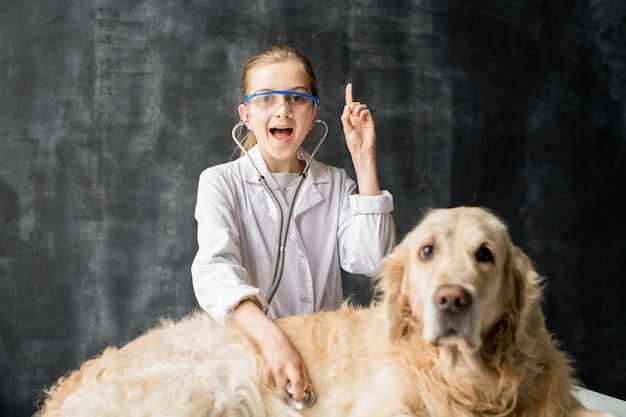 Piccola ragazza veterinaria sveglia in occhiali protettivi che esamina il cane di labrador con lo stetoscopio e che indica verso l'alto