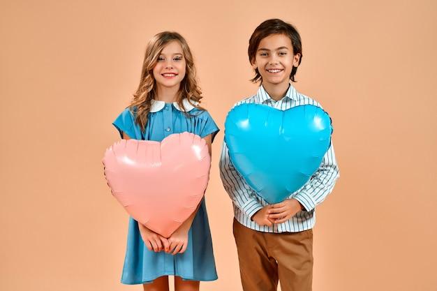 Carina bella ragazza con riccioli in un vestito blu e un bel ragazzo in una camicia stanno tenendo palloncini cuori san valentino isolati