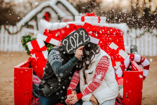 Uomo carino e donna bruna dai capelli lunghi in maglioni invernali, giacche e cappelli di natale seduti in macchina rossa con regali, baci, di fronte alla targhetta 2022. il focus è sulla targhetta. nevicando.