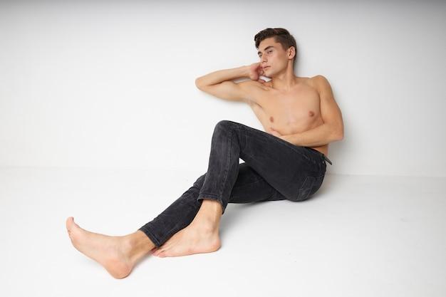 Torso nudo uomo carino seduto sul pavimento isolato parete fiducia in se stessi
