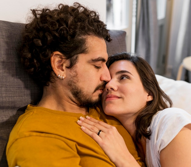 Uomo carino e donna che stringe a sé a letto
