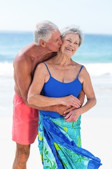 Coppie mature sveglie che abbracciano sulla spiaggia