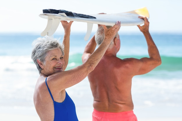 Coppie mature sveglie che tengono una tavola da surf