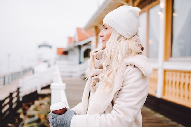 La donna bionda di mezza età sveglia gode del tempo all'aperto al giorno di inverno. la donna indossa una giacca leggera, un cappello, una sciarpa e una bevanda calda.