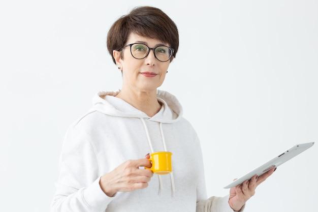 Carina donna di mezza età in abiti casual sta cercando negozi online utilizzando un tablet e tenendo una piccola tazza di caffè gialla su un muro bianco