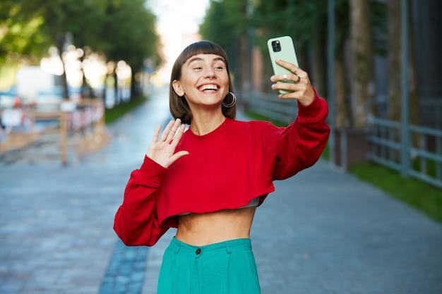 Carina donna millenaria in maglione rosso alla moda che dice ciao al suo telefono, donna che parla tramite web cam attraverso il suo telefono per strada