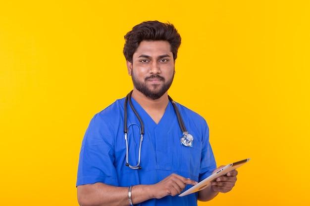 Carino medico di razza mista in una veste blu con uno stetoscopio guardando un tablet basato su un muro giallo. consulenza in linea di concetto. copyspace