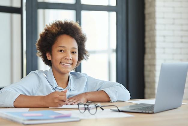 Studentessa adolescente di razza mista carina che sorride alla macchina fotografica usando il laptop mentre prende appunti durante online