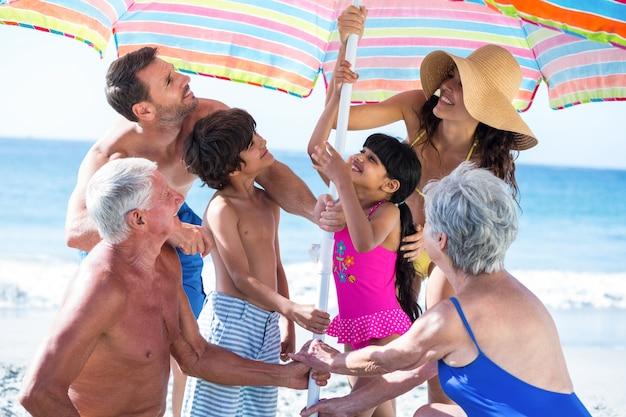 Simpatica famiglia multi-generazione che allestisce il proprio ombrello