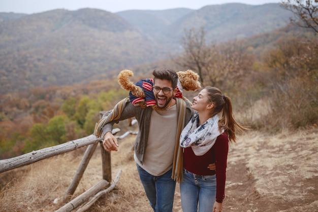 Carina coppia multiculturale vestita casual abbracciare e fare una passeggiata nella natura con il loro cane