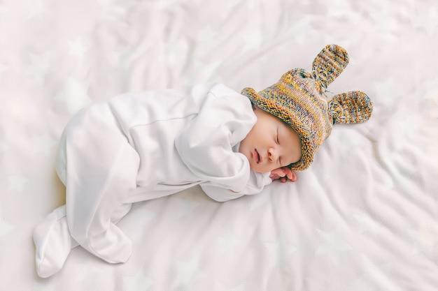 Carino neonato in un buffo cappello con orecchie da coniglio dorme dolcemente in una culla su un lenzuolo bianco morbido, primo piano, vista dall'alto