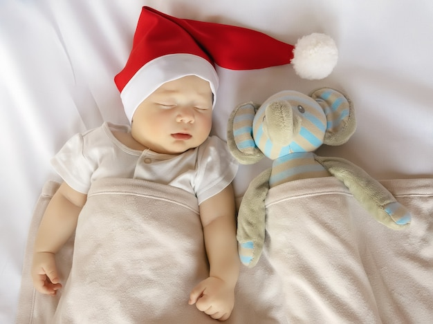 Neonato sveglio in costume di babbo natale che dorme sul foglio bianco con il giocattolo della peluche, vista dall'alto