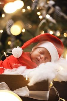 Il neonato sveglio che porta il cappello di santa claus sta dormendo nel contenitore di regalo di natale