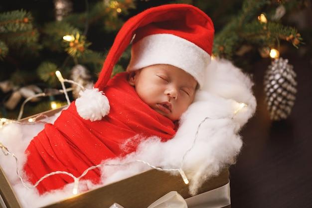 Il neonato sveglio che porta il cappello di babbo natale sta dormendo nella confezione regalo di natale. buon natale e felice anno nuovo.