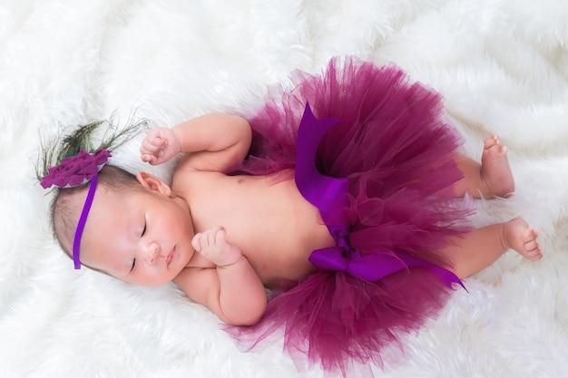 Il neonato sveglio indossa una corona di fiori magenta si trova fasciata