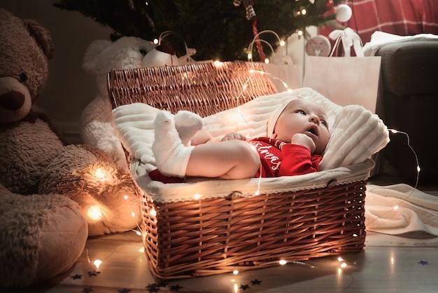 Un bambino neonato sveglio in vestiti di natale che dorme in un cestino sul pavimento contro una decorazione di natale. vigilia di capodanno.