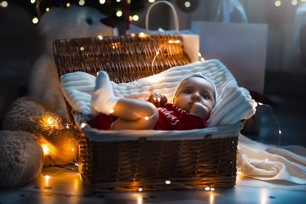 Un simpatico neonato in abiti natalizi che dorme in un cestino sul pavimento contro una decorazione natalizia