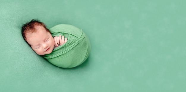 Simpatico neonato che dorme avvolto in una coperta