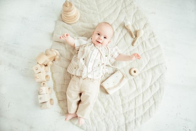 Bambino neonato sveglio sdraiato sul tappeto beige con giocattoli in legno naturale, vista dall'alto