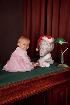 Carina ragazza di un anno in abito rosa in un vecchio ufficio seduto sul desktop. bambino all'interno del ministero degli interni sul tavolo. concetto di istruzione e figli d'affari. sfondo per il sito web. copia spazio