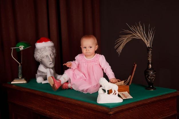 Ragazza carina di un anno in abito rosa in un vecchio ufficio seduto sul desktop. bambino all'interno del ministero degli interni sul tavolo. concetto di istruzione e figli d'affari. sfondo per il sito web. copia spazio
