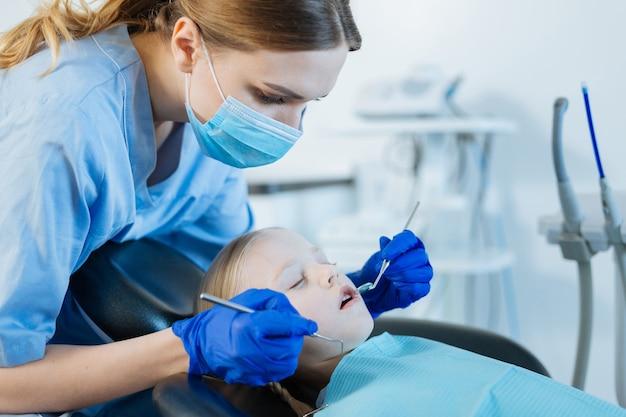 Carina ragazza minuta sdraiata su una poltrona da dentista con gli occhi chiusi e con i denti esaminati da un dentista femmina premuroso utilizzando uno specchio della bocca e una sonda dentale