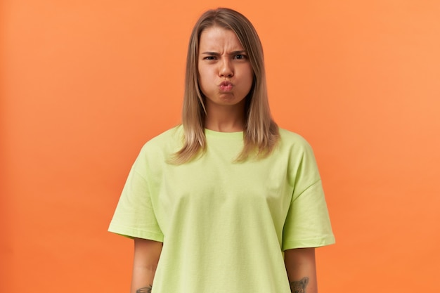 Carina giovane donna giocosa in maglietta gialla che fa una faccia buffa e guarda la parte anteriore isolata sul muro arancione