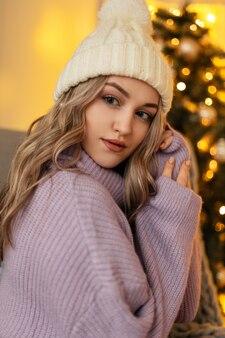 Ritratto carino di una bella ragazza con un'acconciatura in un maglione vintage lavorato a maglia con un cappello di lana sullo sfondo di un albero di natale e luci gialle. vacanze invernali