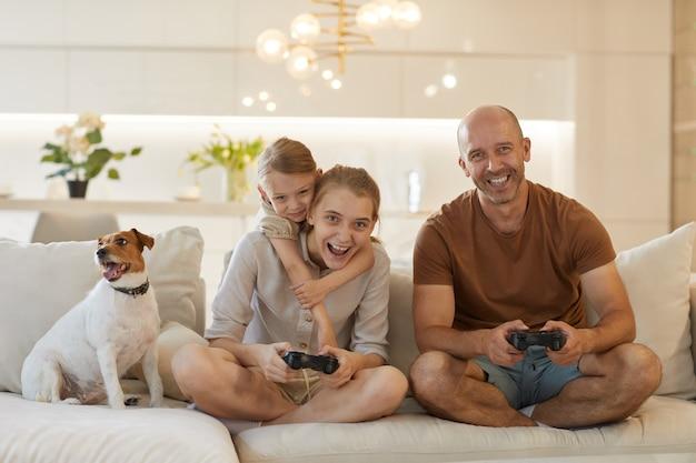 Ritratto sveglio della famiglia moderna felice che gioca insieme ai videogiochi mentre si siede sul divano nell'interno domestico accogliente, uomo maturo sorridente che gode del tempo con due figlie e cane da compagnia