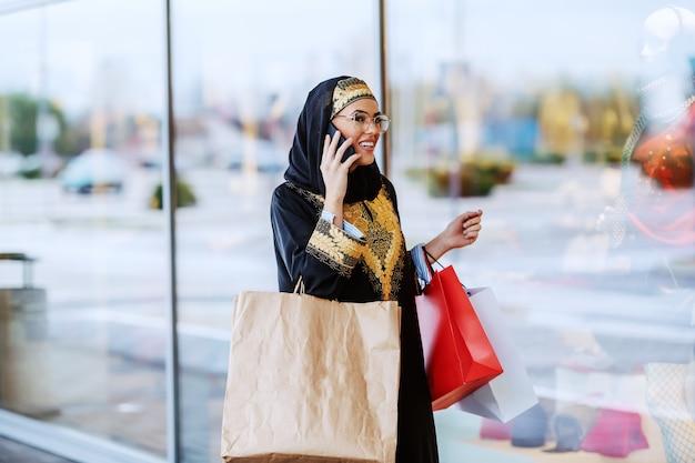 Carina donna musulmana positiva in abbigliamento tradizionale con un bel sorriso che passa dalla finestra del negozio e parla al telefono. nelle mani ci sono le borse della spesa.