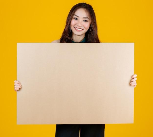 Capelli carini e abbastanza ricci bruna femmina asiatica che tiene il bordo bianco marrone posa alla telecamera con un gioioso per scopi pubblicitari e banner, studio girato isolato su sfondo giallo brillante.