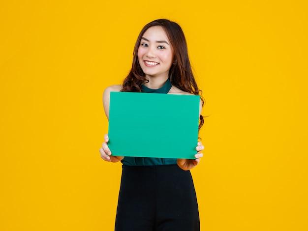 Capelli carini e abbastanza ricci bruna femmina asiatica che tiene il bordo bianco verde posa alla telecamera con un gesto gioioso e positivo per scopi pubblicitari, colpo in studio isolato su sfondo giallo.