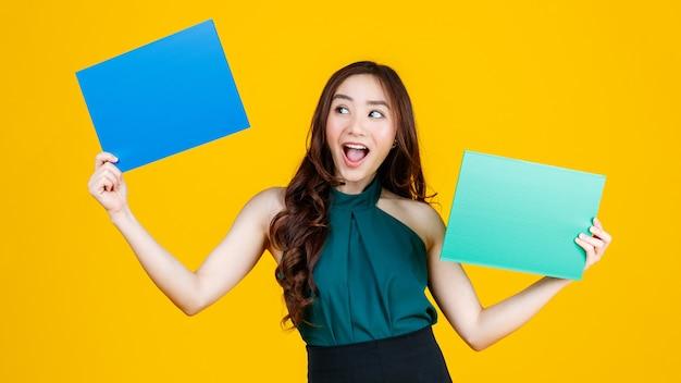 Capelli carini e abbastanza ricci bruna femmina asiatica che tiene il bordo bianco verde e blu posa alla telecamera con un gioioso per scopi pubblicitari, studio girato isolato su sfondo giallo.