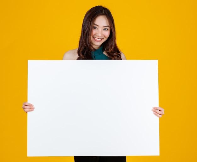Capelli carini e abbastanza ricci asian femmina bruna che tiene e indicando il bordo bianco bianco pone alla macchina fotografica con un gioioso per scopi pubblicitari e banner, isolato su sfondo giallo brillante